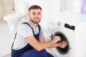 Young plumber fixing washing machine in bathroom