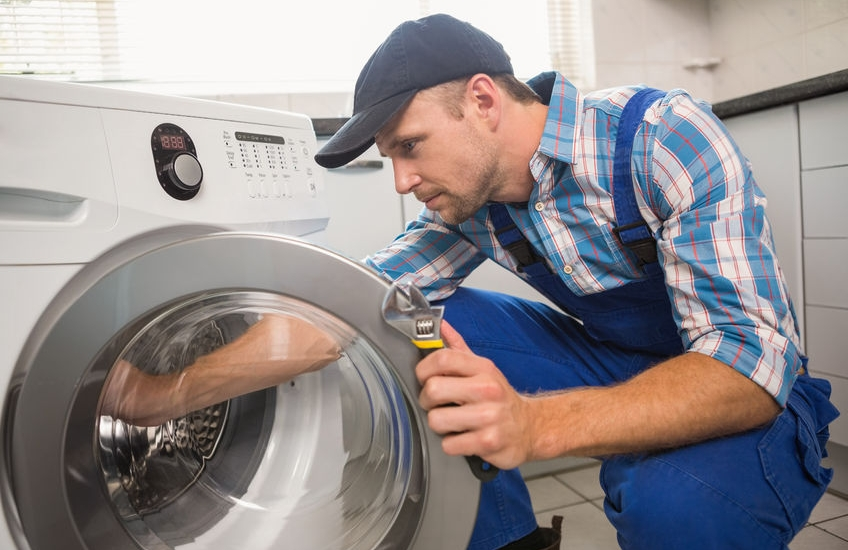33949793 - handyman fixing a washing machine in the kitchen